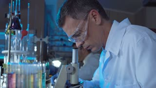 Side view of adult man in white gown and glasses watching in microscope while working in lab