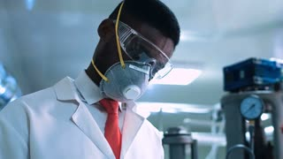 Side view of black scientist in white lab coat, goggles and mask standing next to productional equipment with journal and writing