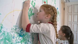 Side view of little redhead girl with braided hair and her older sister doodling with crayons on wall covered in drawings