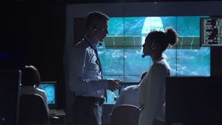 Side view of multiracial man and woman communicating in space flight control center