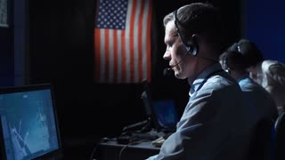 Side view of supervisor man in headset sitting and working in space mission control center. Watching flight of satellite. Elements of this image furnished by NASA