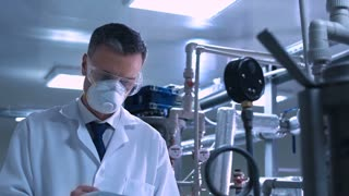 Side view video of male scientist in white lab coat, goggles and mask standing next to productional equipment checking indicators and writing in journal. Middle shot 4K