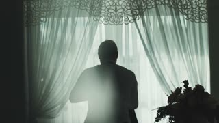 Silhouette of attractive handsome standing near window and dresses