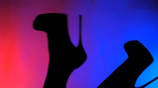 Silhouette of female legs in high-heeled shoes on a background of neon light.