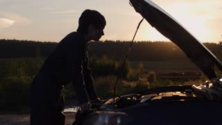Silhouette woman at sundown standing near broken car with opening hood. On the background beautiful forest in sun rays