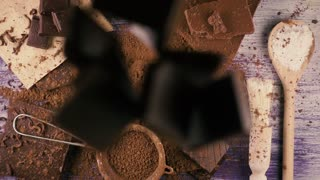 Slices of broken chocolate fall down on cocoa powder, chocolate, a spoon with powdered sugar. Top view. Slow motion