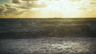 Slow mo a huge wave breaks down on the shore with a lot of splashing in the sunset sun and a cargo ship on the horizon