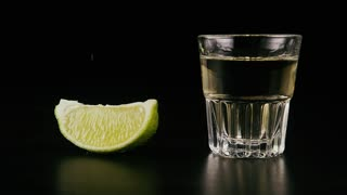 Slow mo. A slice of lime and a shot of tequila on the table and sprinkle the salt on lime