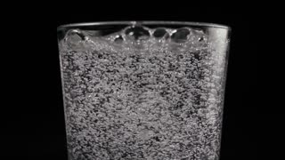 Slow mo. Bubbles from mineral water, soda in a glass on a black background