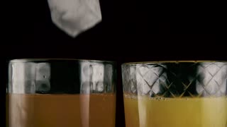 Slow mo. In two glasses with orange drinks falls ice cubes, juice and soda on a black background