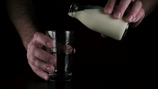Slow mo. Man's hands pour milk from a glass bottle into a glass on a black background