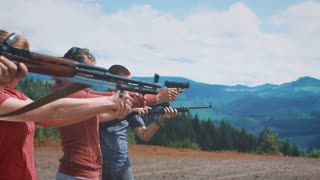 Slow Mo Shot of People Standing in Row Shooting Guns Outside