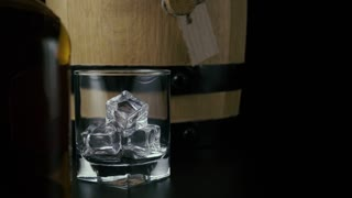 Slow mo. Whiskey pours into a glass with ice, against the background of a barrel for whiskey and a bottle, a black background