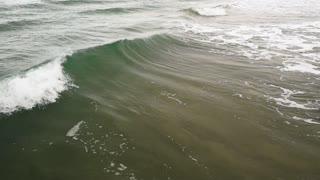 Slow motion a foamy wave rolls by