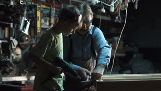 Slow motion adult carpenter man and grandson make a window from wood and screws with a screwdriver