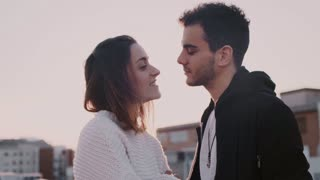 Slow motion beautiful and sensual young couple madly in love, full of real emotions and feelings, kiss and touch noses for eskimo kiss in sunset light on terrace, concept millennial relationship goals