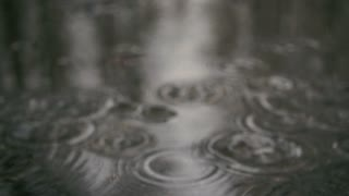 Slow motion. Blurry drops of heavy rain in a puddle on the sidewalk
