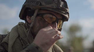 Slow motion, close view, soldier on battlefield having a smoke while other soldiers talking at background