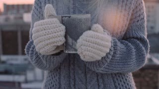 Slow motion dreamy and romantic shot of inspirational cute young girl in knitted sweater and mittens, with adorable pretty hat, blows on hot coffee or tea in cup, drinks and smiles to camera