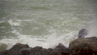 Slow motion large splashes from a crashed wave of boulders on the seashore