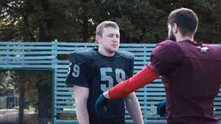 Slow motion of American football player helping his mate to put on jersey before game on field