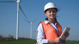 Slow motion of cheerful korean woman with digital tablet wearing hard hat standing against turbines at wind farm on sunny day