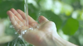 Slow motion of clear water streaming on a human hand. Taking care about environment and natural resources.