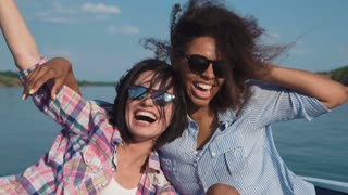 Slow motion of girl weared sunglasses friends laughing in speed motorboat