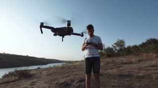 Slow motion of man using black quadcopter while standing on river shore with remote controller