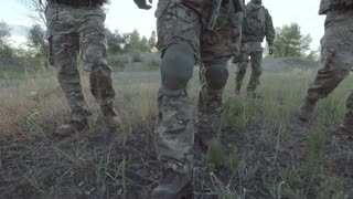 Slow motion of unrecognizable military people with firearms walking on battlefield