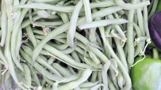 Slow motion. POV point of view - Organic green beans at the local Farmer's Market.