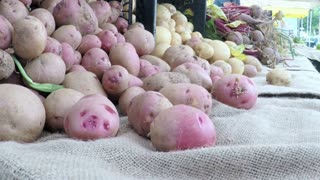 Slow motion. POV point of view - Organic potatoes at the local Farmer's Market.