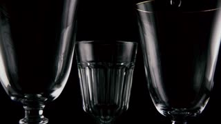 Slow motion. Red white rose wine pour into three different glasses on a black background, focus on white