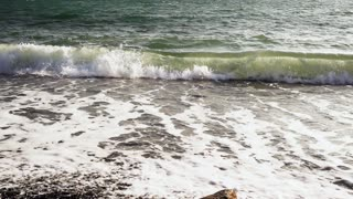 Slow Motion sea wave crashed a pebble beach with foam and spray