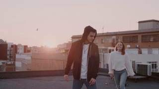 Slow motion shot of beautiful cute couple of teenagers or hipster millennials on romantic date. Girl jumps on boyfriend piggy back ride, they laugh in natural way, enjoy each other company
