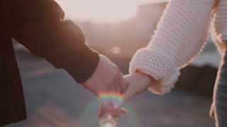 Slow motion soft focus tender and sensual, moving shot of couple holding hands and caressing each other fingers on sunset filled beautiful evening at terrace or rooftop, concept love and relationship