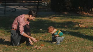 Slow motion toned footage of young mother playing with her baby son with leaves at autumn park. Beautiful family. Love and happiness