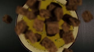 Slow motion. Top view. Fall into a bowl with broth small square toasts of black bread on a black table
