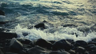 Slow motion waves breaking against rocks on the shore, move the camera up