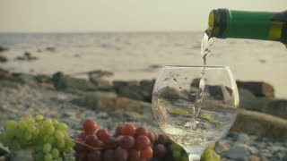 Slow motion white wine from a bottle to pour in a glass on a stony coast against the background a calm sea