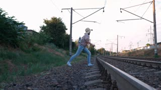 SLOW MOTION: Young beautiful trendy woman in hat Cross the railroad tracks. Railroad ties and stone with traveling girl with backpack running. Dangerous concept
