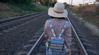SLOW MOTION: Young beautiful trendy woman in hat walking on railroad track. Railroad ties and stone with traveling girl with backpack walking. Summer season