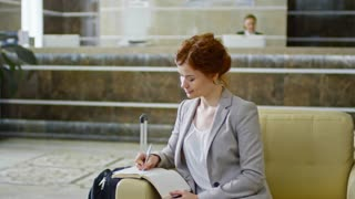 Slowmo of pretty businesswoman sitting in armchair in hotel lobby and writing in organizer while businessman walking to reception
