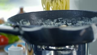 Slowmo of unrecognizable male cook adding cooked spaghetti into hot pan with sauce