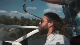 Slowmotion bearded man in sunglasses driving boat with friends on background peoples taking selfie with smartphone mounted on selfie stick