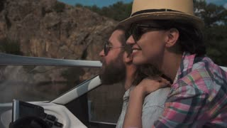 Slowmotion of young couple speeding along in a motorboat with their hair flying in the wind in a close up view