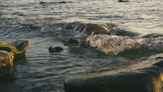 Small waves faintly beating against stones slow motion