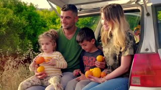 Smiling family farmers with children sitting on pickup truck with harvest orange