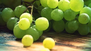Spraying water over ripe fresh green grapes on a wooden table. Close-up slow motion shot