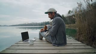Static shot of hipster man in hoodie and cap with best friend puppy on lap, cuddle and pet his dog, while looks at computer laptop and coffee hiking metal cup on boardwalk on lake or river